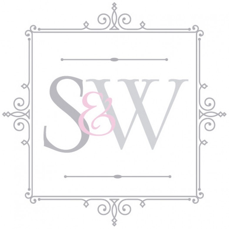A futuristic white console table with blue acrylic cabochons and a polished brass base