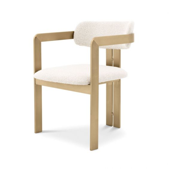 A chic and contemporary brushed brass dining chair upholstered in boucle fabric