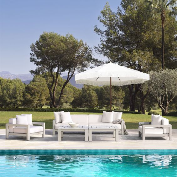 A luxurious outdoor sofa with a sand-coloured frame and natural-toned upholstery