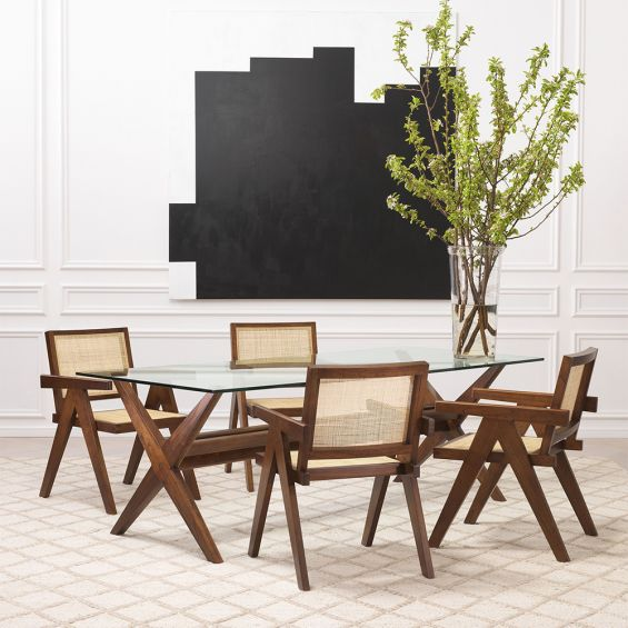 An iconic, brown Jeanneret-inspired dining chair with a rattan seat and backrest