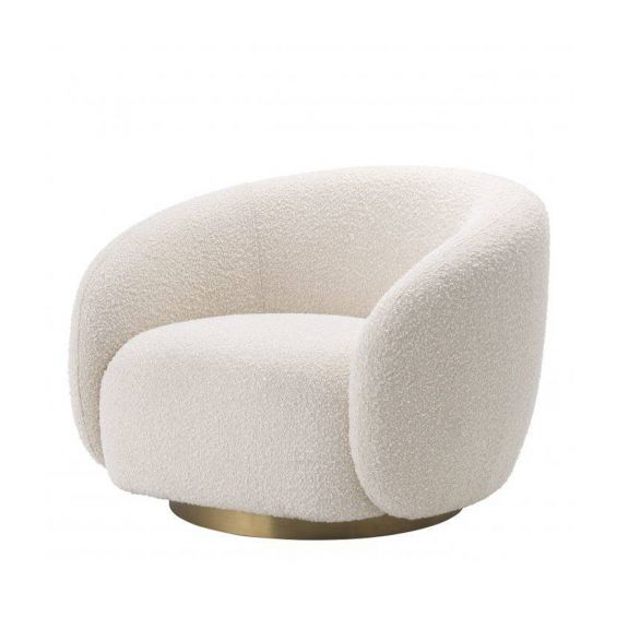 A sumptuous art deco inspired armchair with a brushed brass swivel base