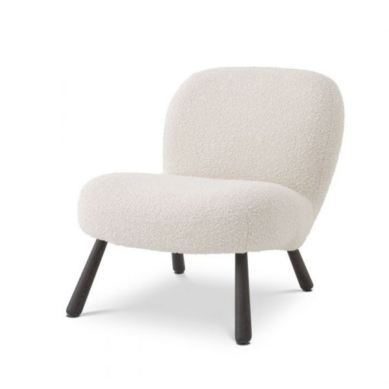 A luxurious boucle cream armchair with splayed, wooden legs