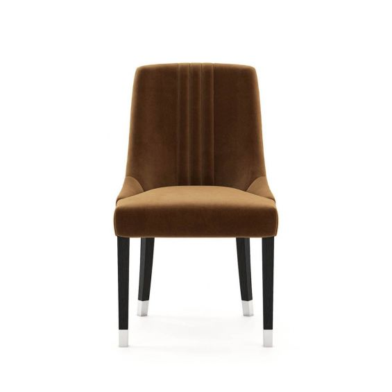 A timelessly elegant dining chair upholstered in velvet with black legs and golden caps. Pictured in Vienna Teja.