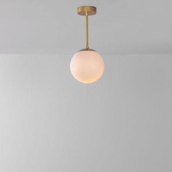 Industrial style glass globe pendant made entirely of solid brass and handblown glass globes with a natural brass finish