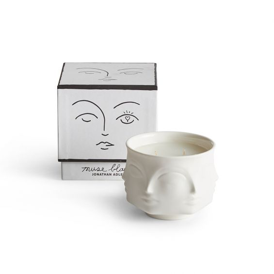 white ceramic candle decorated with faces