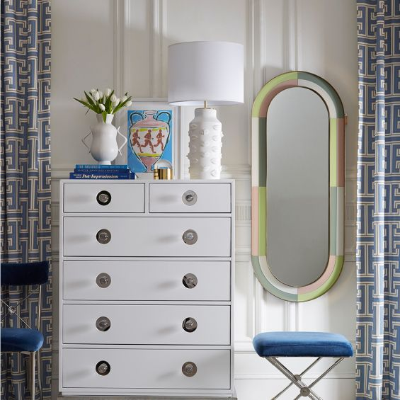 A luxurious capsule-shaped mirror with a multicoloured reverse painted glass frame