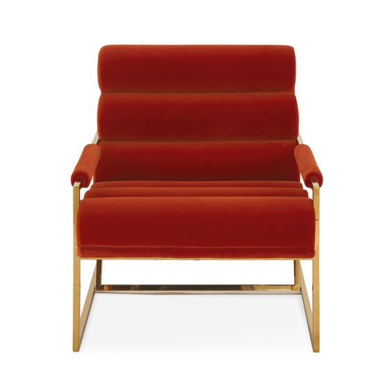 A mid-century modern inspired armchair with burnt orange velvet and a polished brass frame