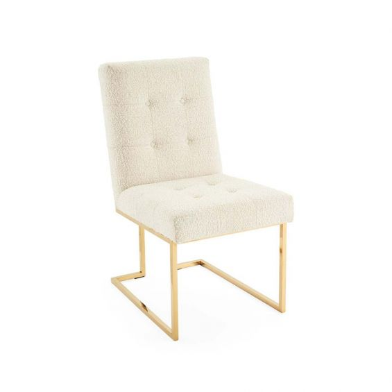 A boucle upholstered dining chair on a brass frame.