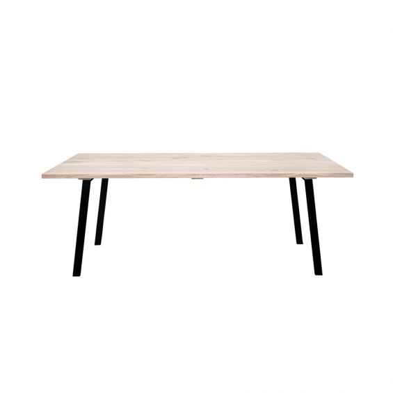 A stylish natural oak table with black iron legs