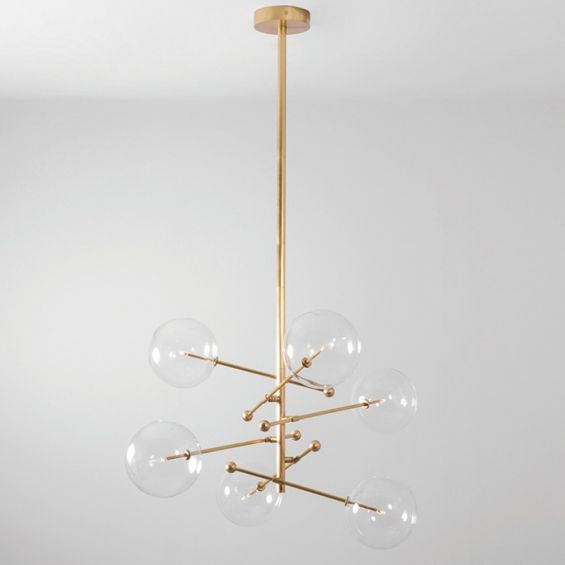Industrial style 6 arm chandelier in a natural brass finish with 6 clear glass globe bulbs