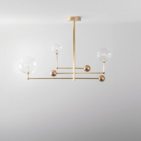 Industrial retro style chandelier with rotational light fixture in a natural brass finish and clear glass globes in different sizes