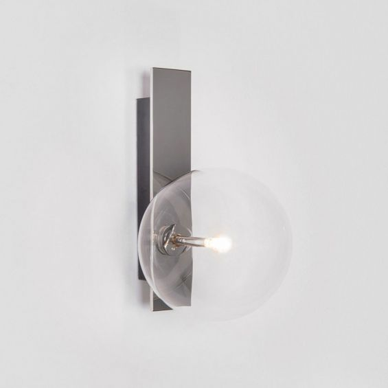 A chic polished nickel wall lamp with a transparent glass lampshade