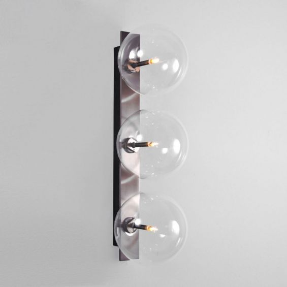 A glamorous industrial-style triple light wall lamp in a black gunmetal finish