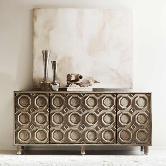 A textured wooden sideboard with four carved geometric patterned doors and finished with nickel plated aluminium legs