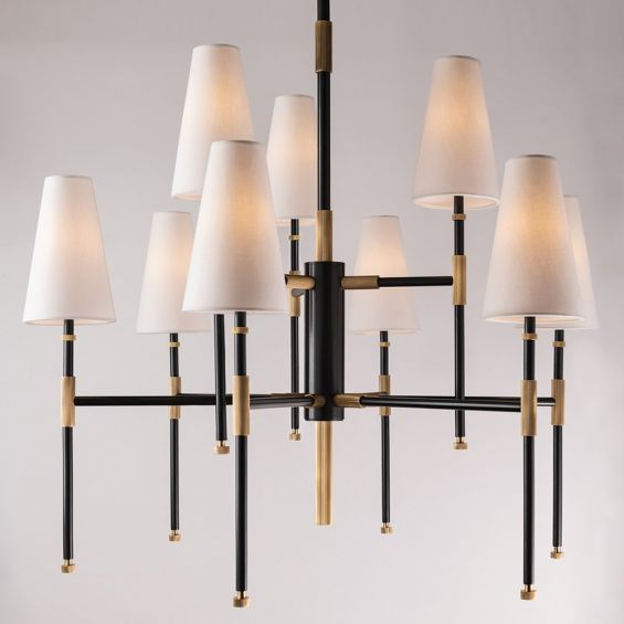 An elegant aged old bronze chandelier with multiple linen lampshades