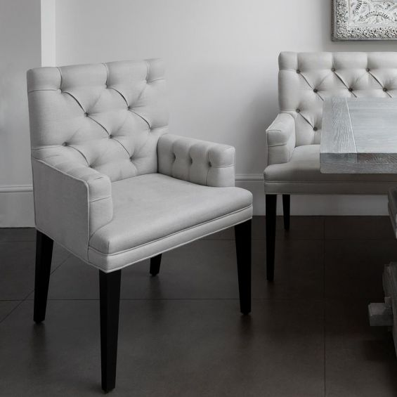 Contemporary, deep buttoned bench dining chair with arms and piping detail