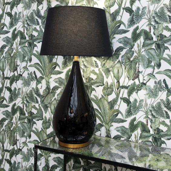 A luxurious black lacquered side lamp with a linen lampshade and brass details
