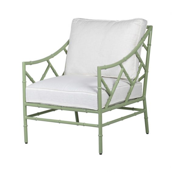 A sage green outdoor sofa chair with linen cushions