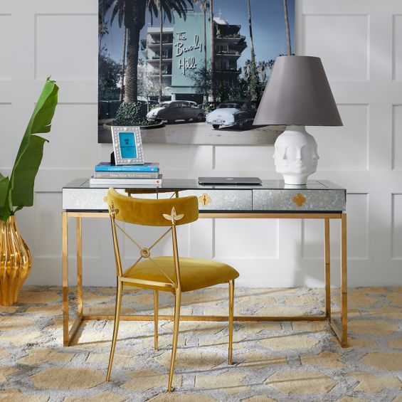 A glamorous, modern desk with a antiqued mirror table top and a polished brass base
