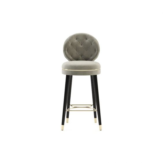 A luxurious Parisian-inspired counter stool with black wooden legs and golden, metal accents