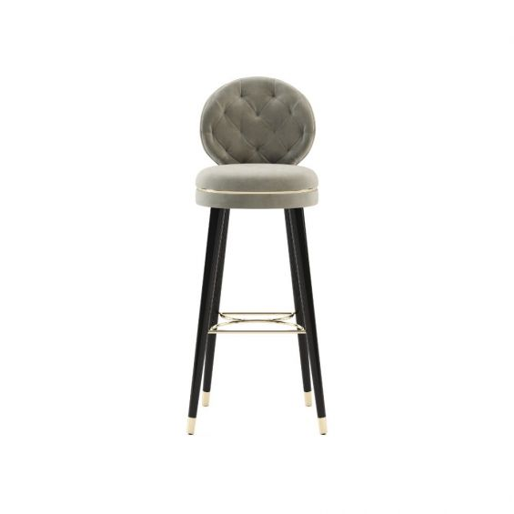 A luxurious Parisian-inspired bar stool with black wooden legs and golden, metal accents