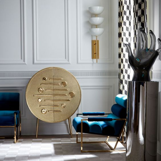 A stylish hand-hammered brass bar cabinet with polished brass legs and interior shelving