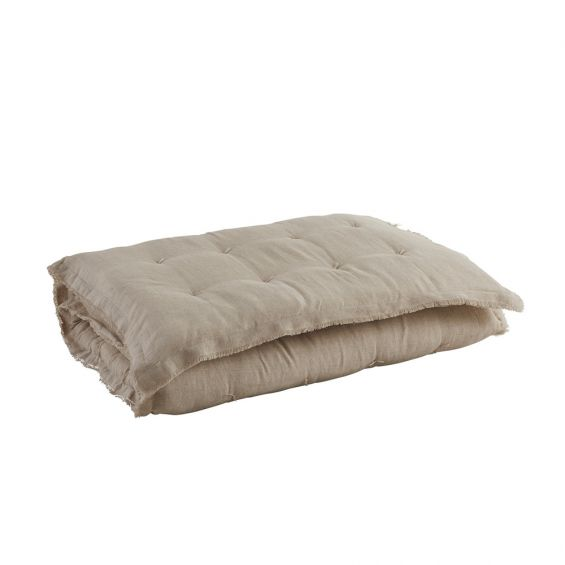 A gorgeous natural-toned quilt with fringed details