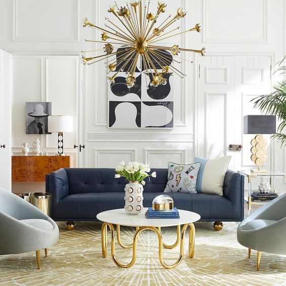 A luxurious modern sofa with navy leather upholstery and brass feet