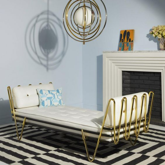A luxurious daybed with a black and polished brass base