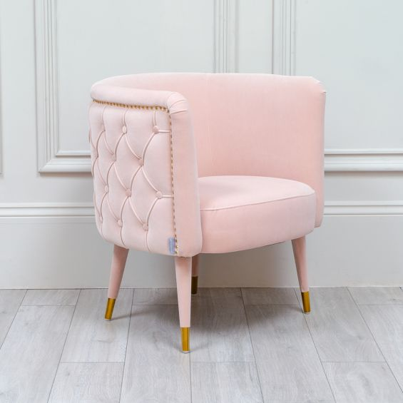 Luxurious pink velvet tub chair with brass studding and tapered legs