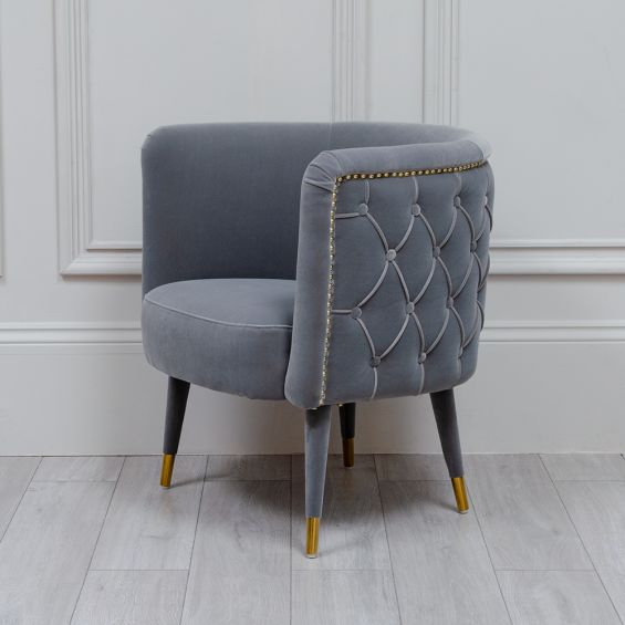 Luxurious grey velvet tub chair with buttoned back seat design and studding