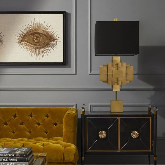 A luxurious sculptural side lamp with layers of solid brass and black lampshade