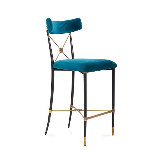 A chic empire-style counter stool in blue velvet fabric