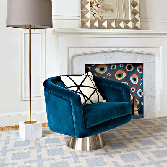 A luxurious blue velvet swivel chair with brushed stainless steel base