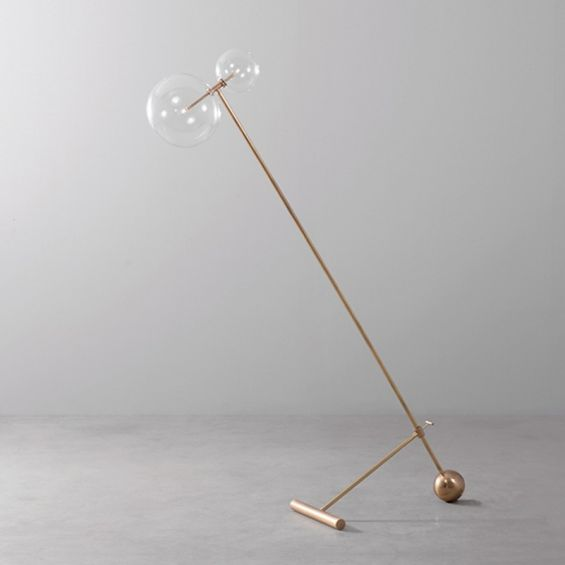 Natural brass industrial style floor lamp with angled design and clear glass globe lampshades with adjustable height