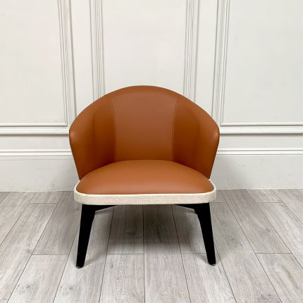 A luxurious leather armchair with glossy black legs and a linen outer back and rim