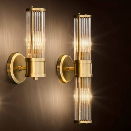 A glamorous wall lamp with an antiqued brass finish and reeded glass