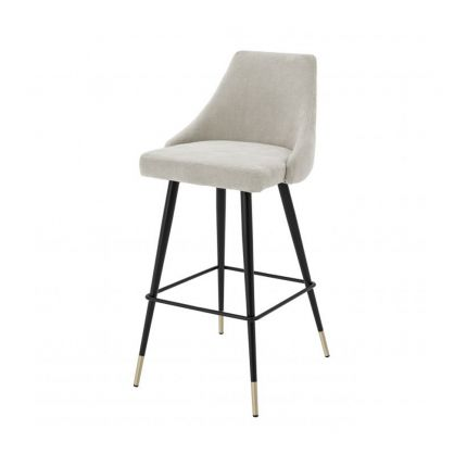A luxurious bar stool in a sand-toned fabric with polished brass detailing