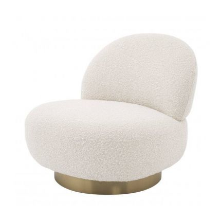 A luxurious boucle armchair with a brushed brass swivel base