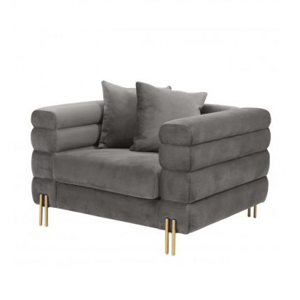 A luxurious grey velvet armchair with brushed brass legs