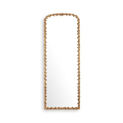 An elaborate vintage brass wall mirror with intricate leaf detailing