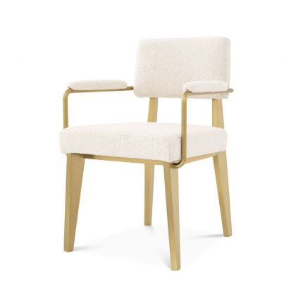 A luxurious brushed brass and boucle dining chair with arms