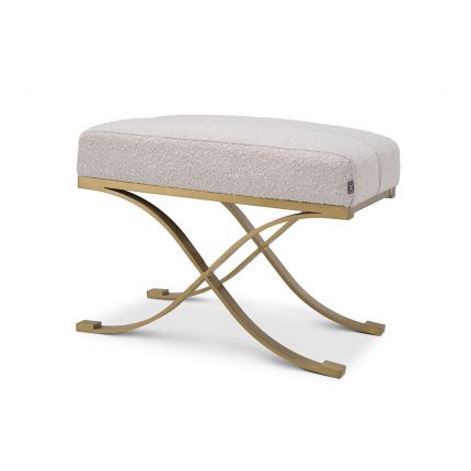 A glamorous stool by Eichholtz with a luxurious boucle cream upholstery and a lustrous brushed brass finish