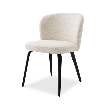 A gorgeous dining chair by Eichholtz with an arched back, tapered black legs and a Pausa Natural upholstery
