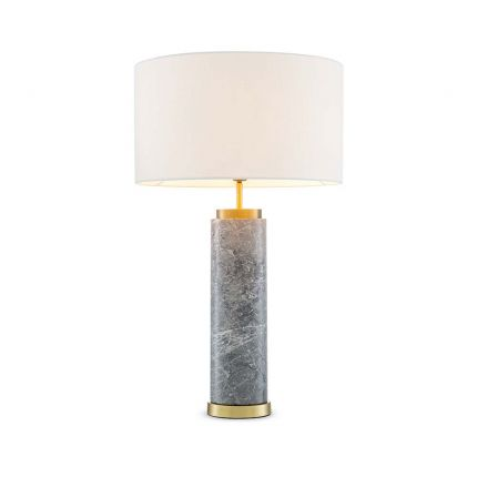 A table lamp with a grey marble cylindrical base as well as an off-white shade and brass finished details.