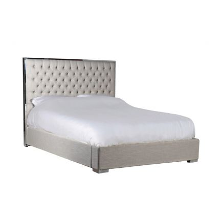 A luxurious linen bed with a deep-buttoned headboard with a metallic boarder
