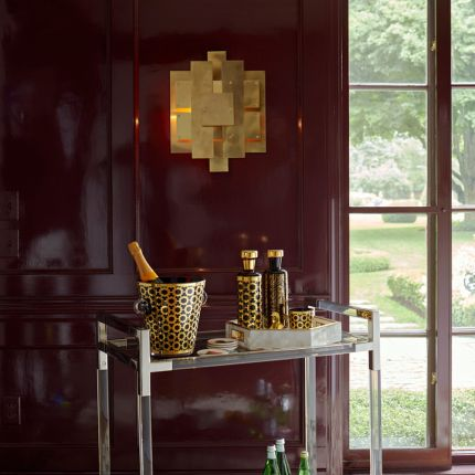 A glamorous industrial-style wall lamp in antique brass