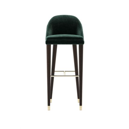 A luxurious bar stool with velvet upholstery and wooden legs with metallic details. Pictured in Vienna Green.