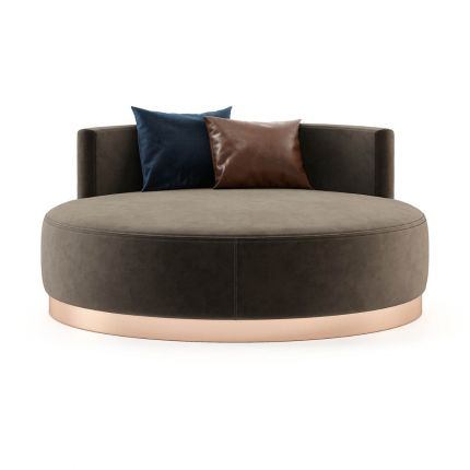 A luxurious round chaise longue with velvet upholstery and a copper-painted stainless steel plinth