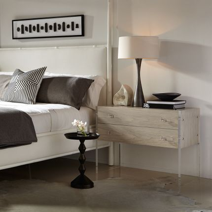 A beautiful two drawer bedside table from Bernhardt featuring a rustic bleached walnut veneer finish and acrylic end panels